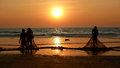 Fishermen dragged ashore network sunset the arabian sea Royalty Free Stock Photo