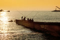 Fishermen on the pier on the background of sunset silhouettes sea and Royalty Free Stock Photography
