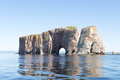 Fishermen at pierced rock can be seen tending their lobster traps just left of the hole in the is a limestone and shale monolith Stock Photos