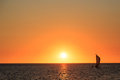 Fishermen in a sailboat at a beautiful warm orange glow sunset Royalty Free Stock Photo