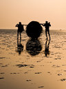 Fishermen at work carrying fishing nets on sea beach Royalty Free Stock Photography