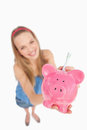 Fisheye view of a young woman putting money in a piggy-bank Stock Image