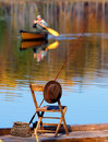 Fishing on a autumn lake pole wicker creel felt hat and wooden chair sit dock an await the arrival of the fisherman who took his Stock Images