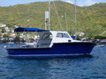 A fishing boat anchored at port elizabeth blue motor used for in and around st vincent and the grenadines Stock Photo
