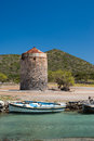 Fishing boat in front of abandoned windmill Royalty Free Stock Photo