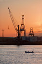 Fishing boat in industrial harbor with cranes at sunset Royalty Free Stock Photo