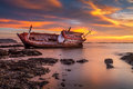 Fishing boat moored on the beach at sunset Stock Photo