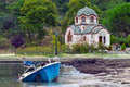 Fishing boat moored on the coast while in the background see the orthodox church of st nicholas olympiada chalkidiki halkidiki Royalty Free Stock Image