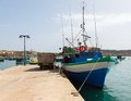 Fishing boat at a pier in the bay marsaxlokk malta Royalty Free Stock Photo