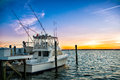 Fishing boat on the pier at sunset on the lake Royalty Free Stock Photo