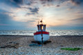Fishing boat on a shingle beach red and white wooden Royalty Free Stock Image