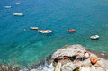 Fishing boats in blue waters small floating near cliffs Stock Photos
