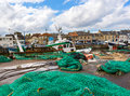 Fishing boats and nets in small harbor in france with laying to dry Royalty Free Stock Image