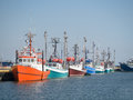 Fishing boats in a row line of at wharf waiting to go out Royalty Free Stock Photo