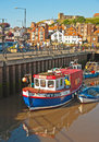 Fishing boats at whitby picturesque on the north east coast of yorkshire with colorful tied up in the harbor Stock Images