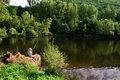 Fishing boy by river young child sitting the on a wood log with an rod lot cantal france Stock Photo