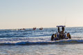 Fishing dive boats launching beach ocean morning activity at durban s vetchies with boat and divers with ski to go out to sea Stock Image