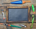 Fishing gear and blackboard on wooden background Royalty Free Stock Images