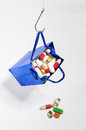 Fishing hook holding a blue bag with medicines full of pills hanging from as if it were bait and droping some Stock Photos