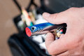 Fishing lure in fisherman hand blue sand and a bag with more lures out of focus at the background Royalty Free Stock Images