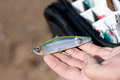Fishing lure in fisherman hand sand and a bag with more lures out of focus Stock Photos