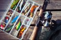 Fishing lures in tackle boxes with spinning rod and net on wooden pier Stock Images