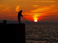 Fishing man view at a alone at wonderful summer golden orange sunset on adriatic sea in croatia horizontal color photo Royalty Free Stock Photo
