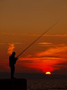 Fishing man view at a alone at wonderful summer golden orange sunset on adriatic sea in croatia vertical color photo Stock Photo