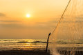 Fishing net ocean beach sunset on the with orange sky and clouds and poles and tied to it industry copy space in the Royalty Free Stock Images
