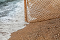 Fishing net on sandy beach at sea waves closeup photo of Royalty Free Stock Images