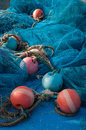 Fishing nets and buoys in blue red scattered on board of a vessel Stock Photos