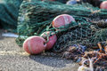 Fishing nets lying on the wharf at sunrise at the port of Norway. Royalty Free Stock Photo