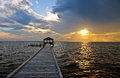 Fishing pier and dock at sunset an empty an incoming storm overlooking the sound the outer banks of north carolina Royalty Free Stock Images