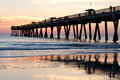 Fishing pier sunrise at a on the ocean Royalty Free Stock Photos