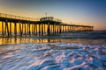 Fishing pier and waves on the atlantic ocean at sunrise in ventn ventnor city new jersey Stock Image