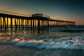Fishing pier and waves on the atlantic ocean at sunrise in ventn ventnor city new jersey Stock Photo