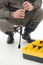 Fishing is always pleasure fisherman in grey watertight costume and black waders holding the spinner and sitting near the box for Stock Image