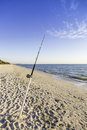 Fishing pole against ocean at sunset Royalty Free Stock Photos