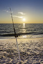Fishing pole against ocean at sunset Stock Photos