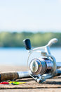 Fishing rod on jetty close to lake Royalty Free Stock Photo