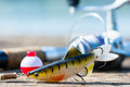 Fishing rod, lure, and hook on jetty Royalty Free Stock Photo