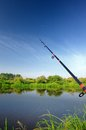 Fishing rod spinning rod over lake a a with green bushes and trees in the background Royalty Free Stock Photos