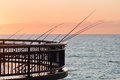 Fishing rodes on a pier at sunrise new brighton new zealand Stock Photos