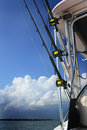 Fishing rods on boat three with reels a luxury ready for use copy space fluffy cloud blue sky Stock Images