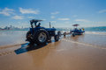 Fishing ski boat beach tractor grounded on the sand with ready to winch the vessel onto its trailer with the blue sea ocean Stock Photography