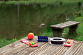 Fishing supplies on a table near a lake Royalty Free Stock Photo