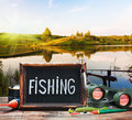 Fishing tackle and a blackboard on background of lake at sunset Stock Photo
