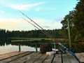 Fishing tackle ready for fishing on a pontoon on the background of the lake in the woods on a wooden pontoon Royalty Free Stock Photography
