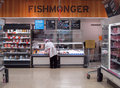 A fishmonger at a fish counter in the fish department of sainsbury s supermarket bedford united kingdom Royalty Free Stock Photos
