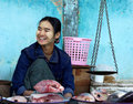 A fishmonger sell some fishes with traditional scales in the wet market on january in bagan market myanmar Stock Image